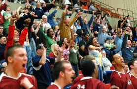 Photograph of a large, diverse group of cheering students, standing up and fist-pumping on the bleachers of a basketball game.