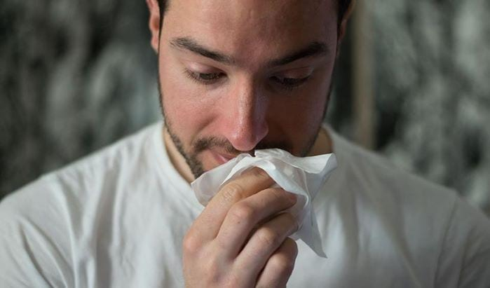 Man blowing his nose with a tissue