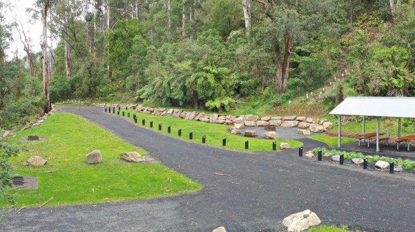 A vibrant green grassy area with a gravel road through the middle leading to a metal picnic shelter.