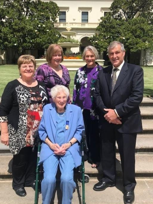 Eulalie sits on her walker surrounded by her daughter Aliison, left, and three other adults on the grounds of Government House, Melbourne.