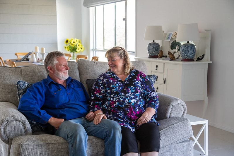 Kevin and Miulusa Giles sit on their couch in their home