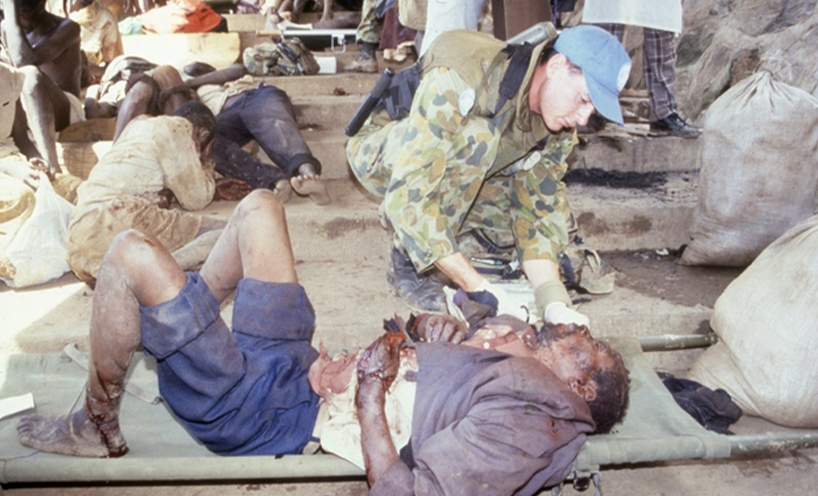 Trooper Jon Church treats a wounded refugee at Kibeho refugee camp April 1995